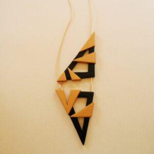Colgante con forma triangular en oro y negro.