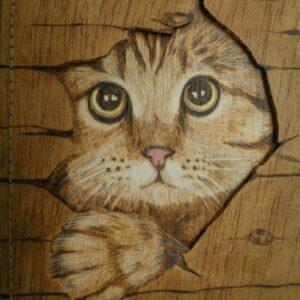 Funda para libretas pirograbada con la imagen de un gatito.